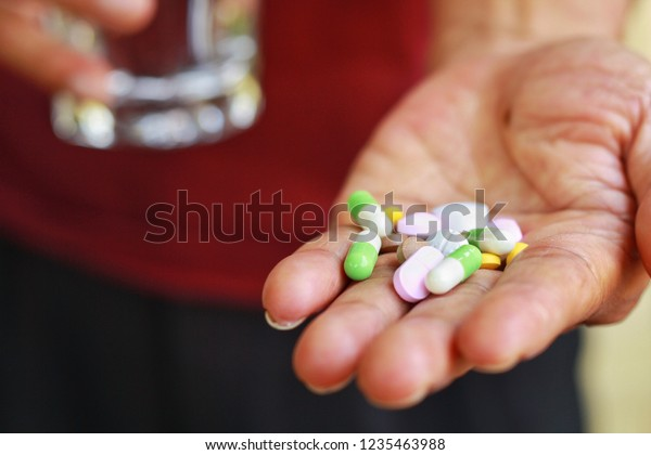 Elderly Asian man holding pills(tablet and capsule) and glass of water in hands taking a lot of medicine, supplements or antibiotic antidepressant painkiller medication Hope for cure,close up view.