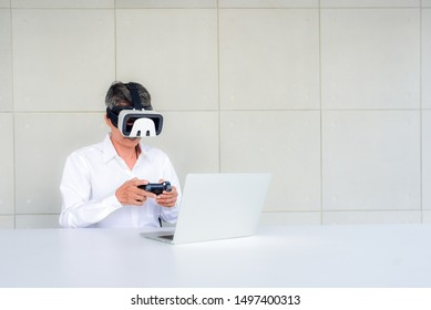 An elderly Asian man is playing a game with Vr glasses technology  combined with Joystick Wireless using fun laptops. Causing older to not feel lonely and in mental health