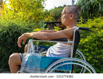 Elderly Asian man suffering from pain in the urinary system sitting on wheelchair outdoors. Diseases for men; Enlarged prostate gland .Urinary catheter.