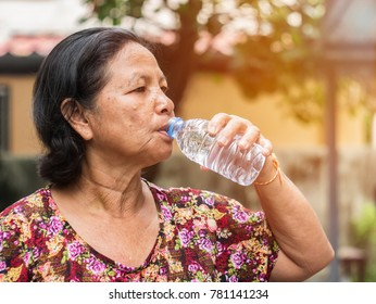 The elderly asian woman drinking water from bottle in park