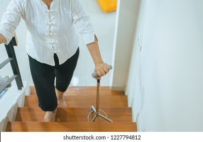 Elderly asian woman holding sticks while walking up stair at home