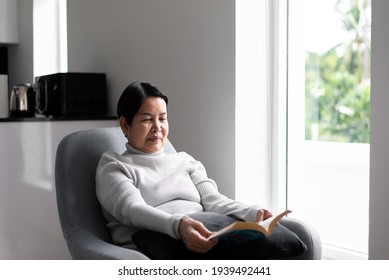 Elderly asian woman reading a book at home,Relax time,Senior lifestyle concept,Long sighted