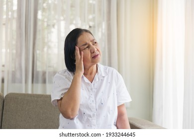 Elderly Asian woman sitting and having a headache and touching her head with her hands at home. Retirement, quarantine and health care concept