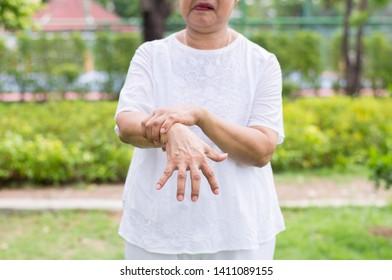 Elderly asian woman suffering with parkinson's disease symptoms