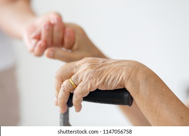 Elderly asian woman using a cane at home with caregiver take care