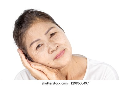 elderly asian woman with wrinkle and freckle on face include white clothes and black hair 60-70 years old in studio head shot of beauty or serenity concept