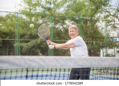 Elderly Asian women are playing tennis for happy health.