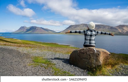 Elderly Backpacker women trekking, traveling, watching a mountain view and feel freedom summer in Iceland.Travel vacation and summer time concept.