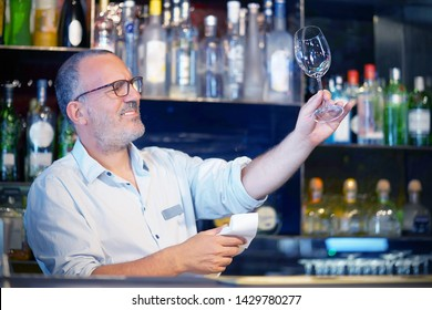 Elderly bartender cleans the glass. A handsome bartender polishes a glass of wine glasses. The concept of service.