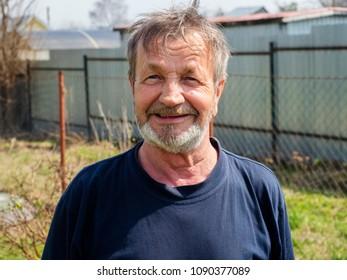 elderly bearded man gardener in his garden