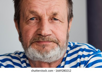 Elderly bearded man in a vest close-up face