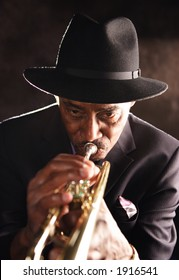 Elderly black man playing a trumpet. He has a soulful countenance.