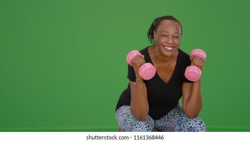 An elderly black woman lifts weights on green screen