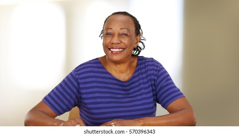 An elderly black woman smiling at the camera