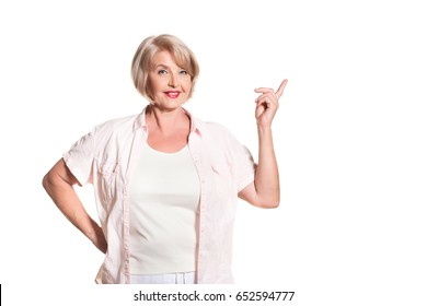 Elderly blond woman smiling over a white background and showing sighs, space for text