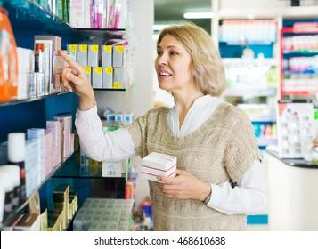 Elderly blonde female near counter in pharmacy drugstore