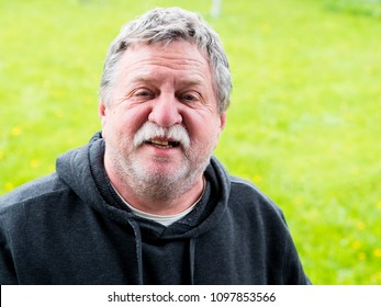 Elderly brooding mustachioed man in nature portrait
