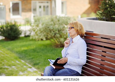 Elderly business woman thoughtfully running outdoors.