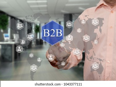 An elderly businessman chooses B2B, Business to business on the touch screen with a blur office background