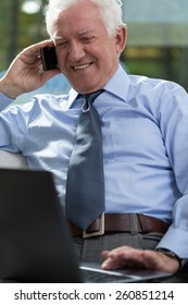 Elderly businessman working on laptop and talking phone
