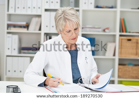 Elderly businesswoman working at her desk at the office reading through notes in a binder