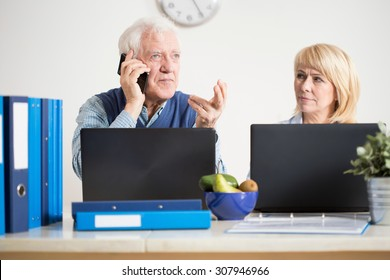 Elderly busy man transacting business cases on the phone