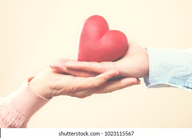 Elderly care concept. Young male doctor from health care facility passing a heart shape figure to senior woman. Close up of hands holding abstract love sign in nursing home. Background, copy space.