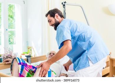 Elderly care nurse helping senior man from wheelchair to bed