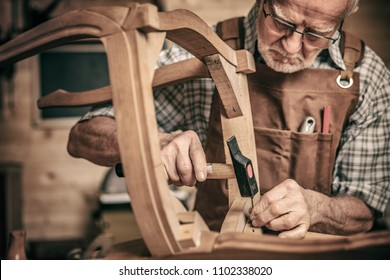 elderly carpenter builds a classic style chair