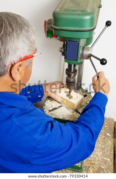An elderly carpenter in a drill in a joinery