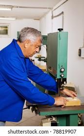 An elderly carpenter on a band saw in a carpenter