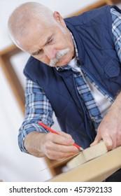 an elderly carpenter at work