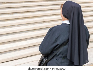 An elderly catholic nun facing high white marble stairs