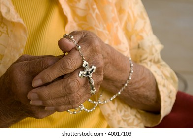 elderly caucasian hands holding a silver rosary