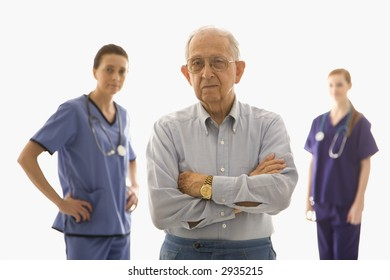 Elderly Caucasian male in foreground with two Caucasian females in the background.