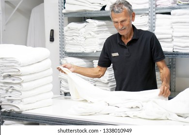 Elderly caucasian male laundry hotel worker folds a clean white towel. Hotel staff workers. Hotel linen cleaning services.