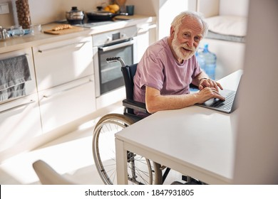 Elderly Caucasian man in the wheelchair sitting at the table in front of the laptop