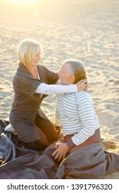 Elderly caucasian wife hugging senior husband and sitting on plaid on sand beach in sun rays. Concept of happy pensioners on picnic.