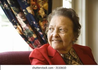 Elderly Caucasian  woman by window at retirement community center.