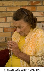 elderly caucasian woman with hands folded in prayer while holding a rosary