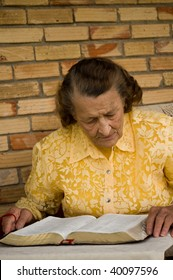 elderly caucasian woman with hands holding Bible as she reads studies the Word