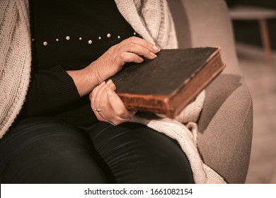 An Elderly Caucasian Woman Holds An Antique Book In Her Hands. Closed Book In An Old Dark Cover With Aged Pages. Selective Focus On Woman's Hands. Close Up. Toned Image