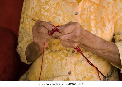 elderly caucasian woman knitting with burgundy wool yarn