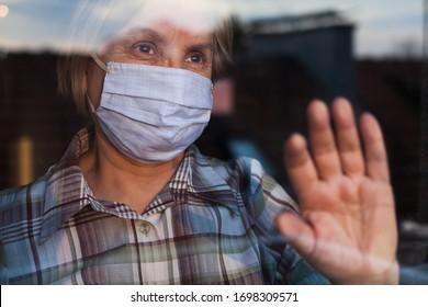 Ältere, kaukasische Frau mit handgefertigter Schutzmaske, zu Hause unter Quarantäne, mit Traurigkeit in ihren Augen nach draußen schauend, selbstisolierend aufgrund der globalen COVID-19-Coronavirus-Pandemie