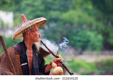 Elderly Chinese fisherman in traditional clothes smoke cigaret.