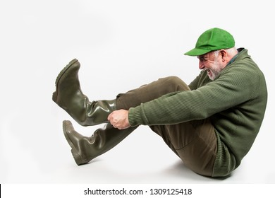 An elderly, clumsy hunter has problems with putting on his rubber boots.