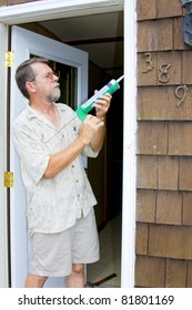 Elderly contractor caulking around glass door frame, sealing from possible air leaks, conserving energy
