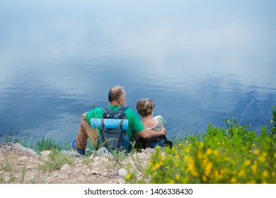 elderly couple with backpacks sits on the mountain. Senior couple walking in nature