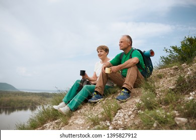 elderly couple with backpacks travels around mountains. Senior couple walking in nature