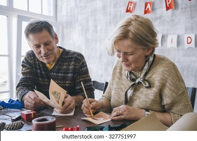 Elderly couple of blonde woman and brunet man painting Christmas cards together